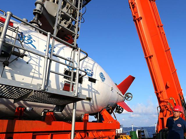 """4月26日,专业人员进行A型架操作,""""蛟龙""""号载人潜水器缓缓推出准备下潜。"""