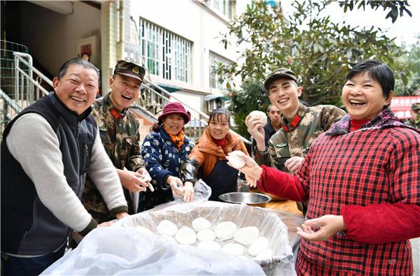 图为2月19日,在重庆银泉养老院,武警官兵正在和老人们一起做糍粑。唐志勇摄.jpg